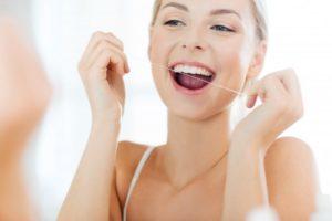 a woman flossing her teeth