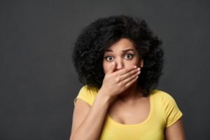 Concerned woman covering her mouth with her hand